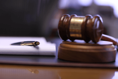 Color photo of gavel alongside pen resting on legal notepad